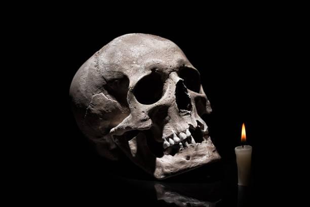 Cráneo humano con quema vela en fondo negro con reflejo de cerca - foto de stock