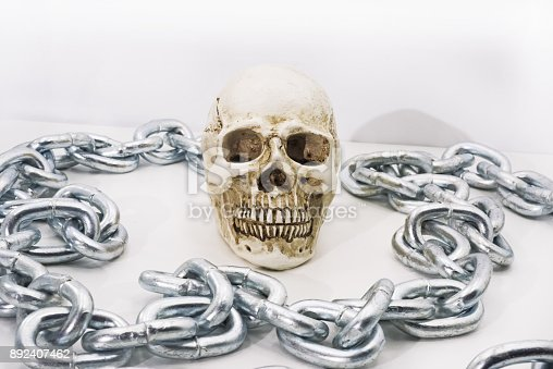 1176385551istockphoto Human skull with iron chain. 892407462