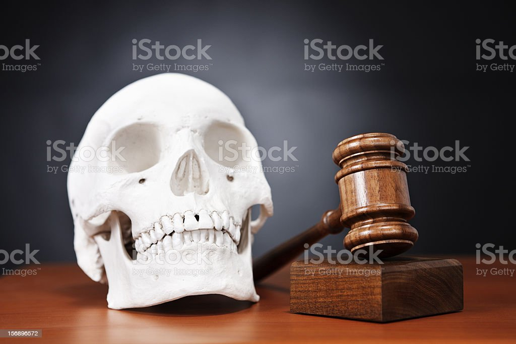 Human skull with judge's gavel on black: harsh justice stock photo