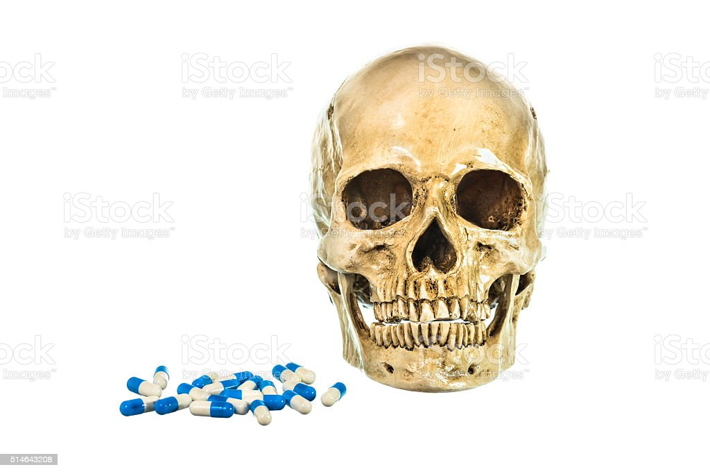 Human skull with pill on white background stock photo