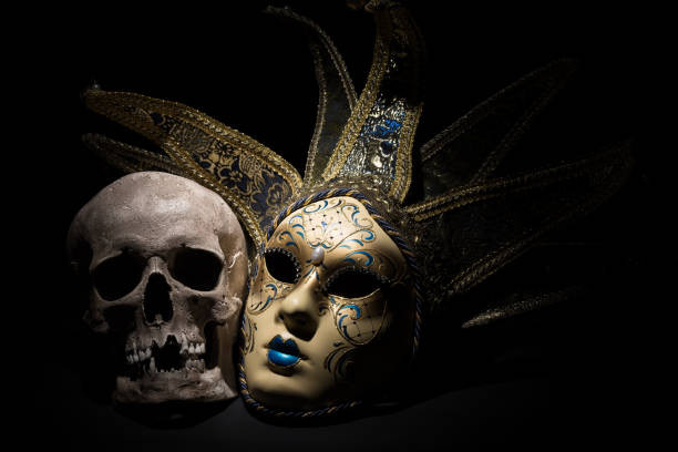 Human skull with venetian mask on a black background. Theater and drama concept stock photo
