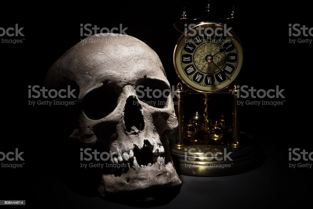 Cráneo humano con reloj vintage de cerca sobre fondo negro - foto de stock