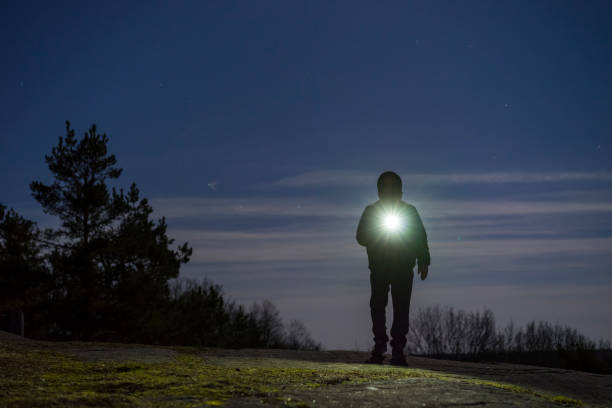 Human standing outdoor at night with flashlight and hoodie on head stock photo