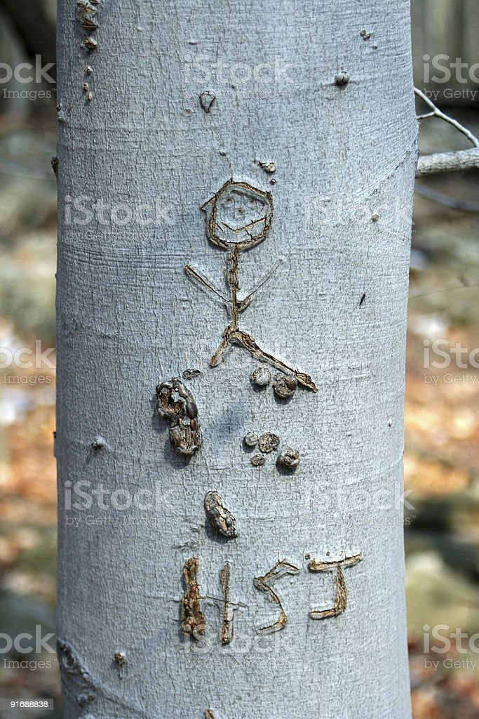 Human stick figure carved in a tree stock photo