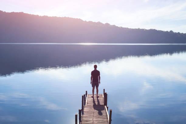 human strength or psychology concept, man standing on pier - ich will stock-fotos und bilder
