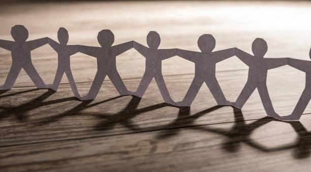 menschliches team von papierkettenmenschen. - scyther5 stock-fotos und bilder
