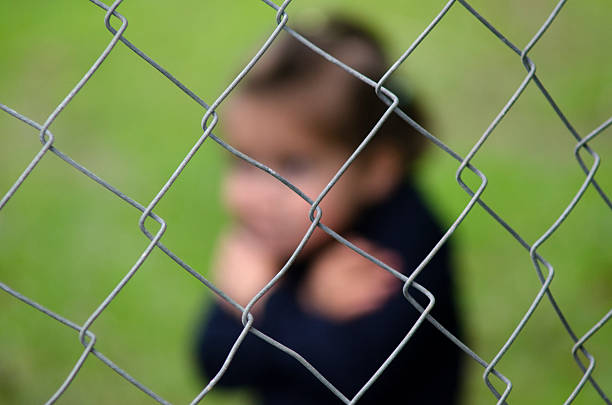 Human Trafficking of Children - Concept Photo Missing kidnapped, abused, hostage, victim girl alone in emotional stress and pain, afraid, restricted, trapped, call for help, struggle, terrified, threaten, behind a fence locked in a cage cell trafficking stock pictures, royalty-free photos & images