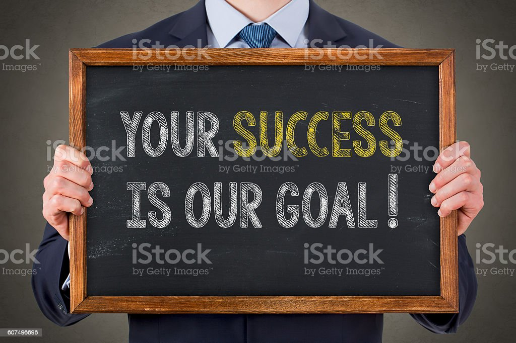 Human Writing Your Success Is Our Goal on Chalkboard stock photo