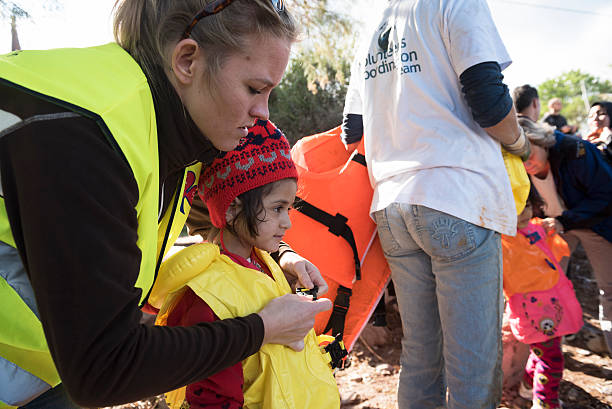Humanitarian volunteer assisting migrants traveling to Europe stock photo