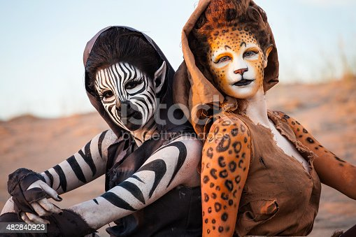 Cheetah & Zebra Woman sitting in the Desert together (Stock Image)