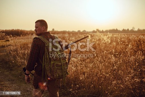Humans back in checkered shirt with military backpack and shotgun in his hand, in the sun light. It's  a soldier hiding into the fields, or a hunter, walking in the grass and searching for prey
