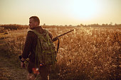 istock Humans back in checkered shirt with military backpack and shotgun in his hand, in the sun light. It's  a soldier hiding into the fields, or a hunter, walking in the grass and searching for prey 1199168076
