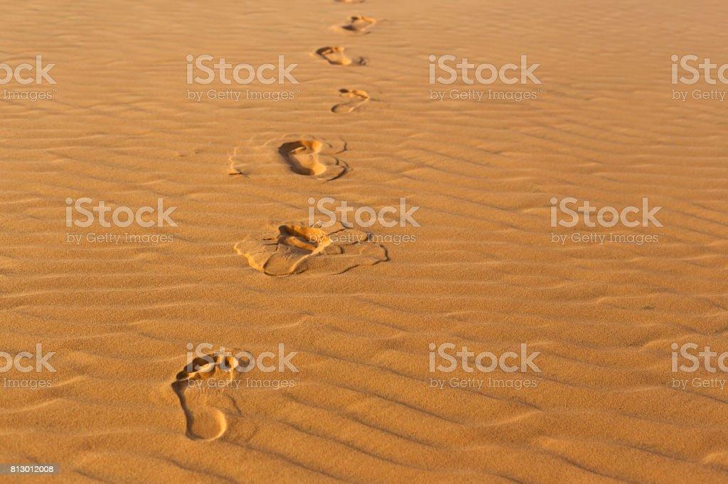 Menschliche Fußabdrücke auf dem welligen Sand in der Wüste – Foto