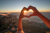 Close up on human's hands making a heart shape finger frame on Cape Town's landscape. People travel love concept.