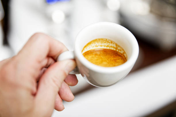 menschen hände halten tasse kaffee vor verschwommenem hintergrund - mokkatassen stock-fotos und bilder