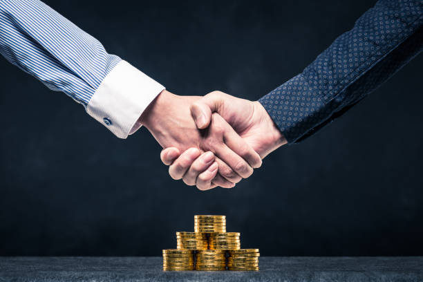 humans share a handshake with a pile of gold coins - deposition stock pictures, royalty-free photos & images