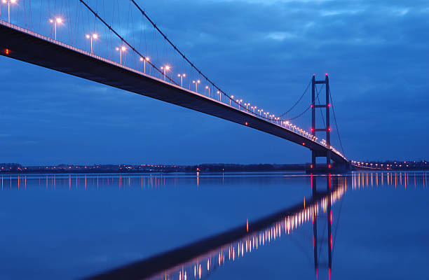 Humber bridge glowing at night The Humber Bridge in Hull, East Yorkshire at dusk. hull stock pictures, royalty-free photos & images