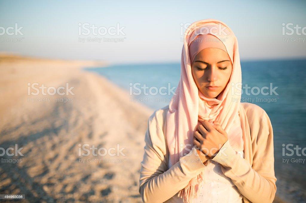 Humble muslim woman praying on the beach.Spiritual religious woman stock photo