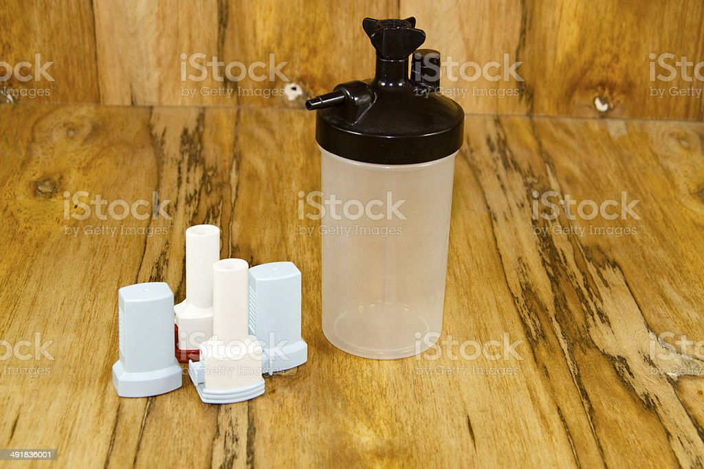 Humidifier bottle with Asthma Inhaler on wooden background stock photo