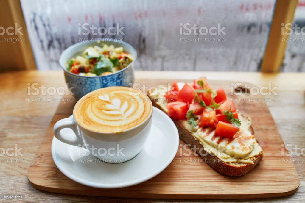 Hummus and tomato sandwich, salad and fresh hot cappuccino coffee bildbanksfoto