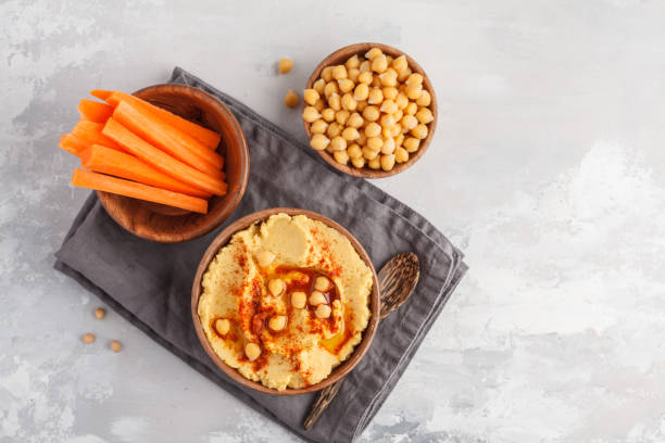 Hummus, fresh carrot sticks and boiled chickpeas in wooden bowls. Vegan food concept, light background, copy space, top view stock photo