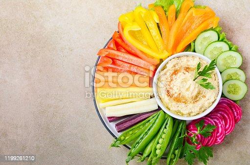 Hummus platter with assorted vegetable snacks. Healthy vegan and vegetarian food. Top view, flat lay, copy space.