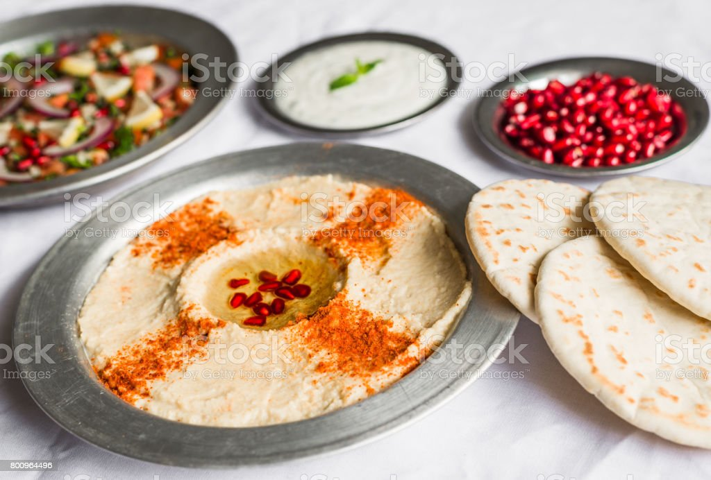 Hummus, tabbouleh, and Arab pita bread with pomegranate seeds and white sour cream sauce against white background. Selective focus. stock photo