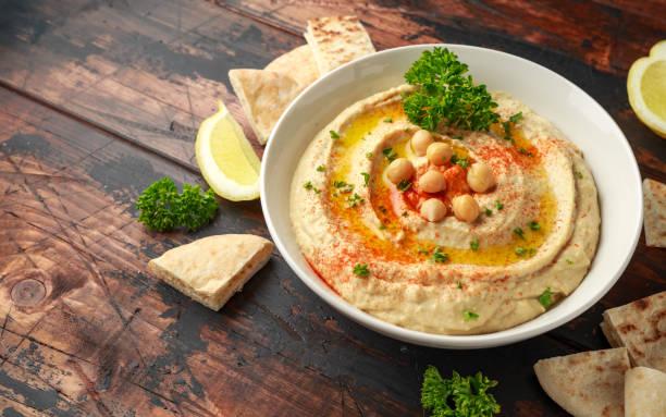 Hummus with olive oil, paprika, lemon and pita bread stock photo