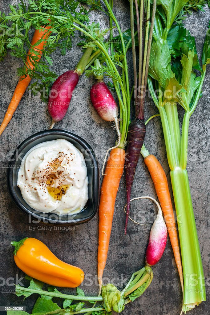 Hummus with Raw Vegetables over Slate Vertical Top View stock photo