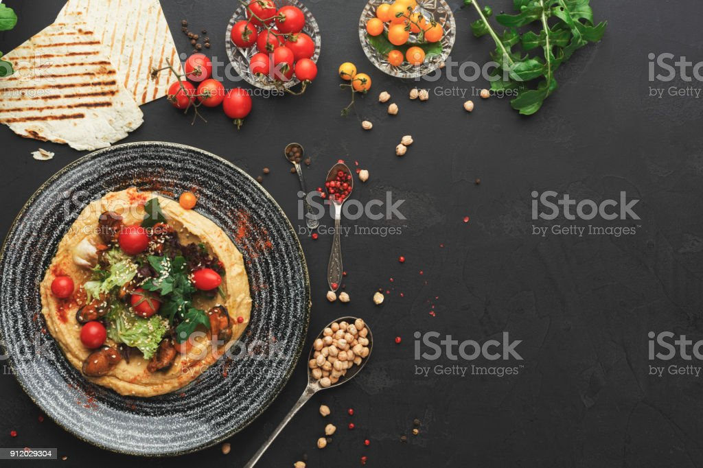 Hummus with vegetables and seafood on black background stock photo