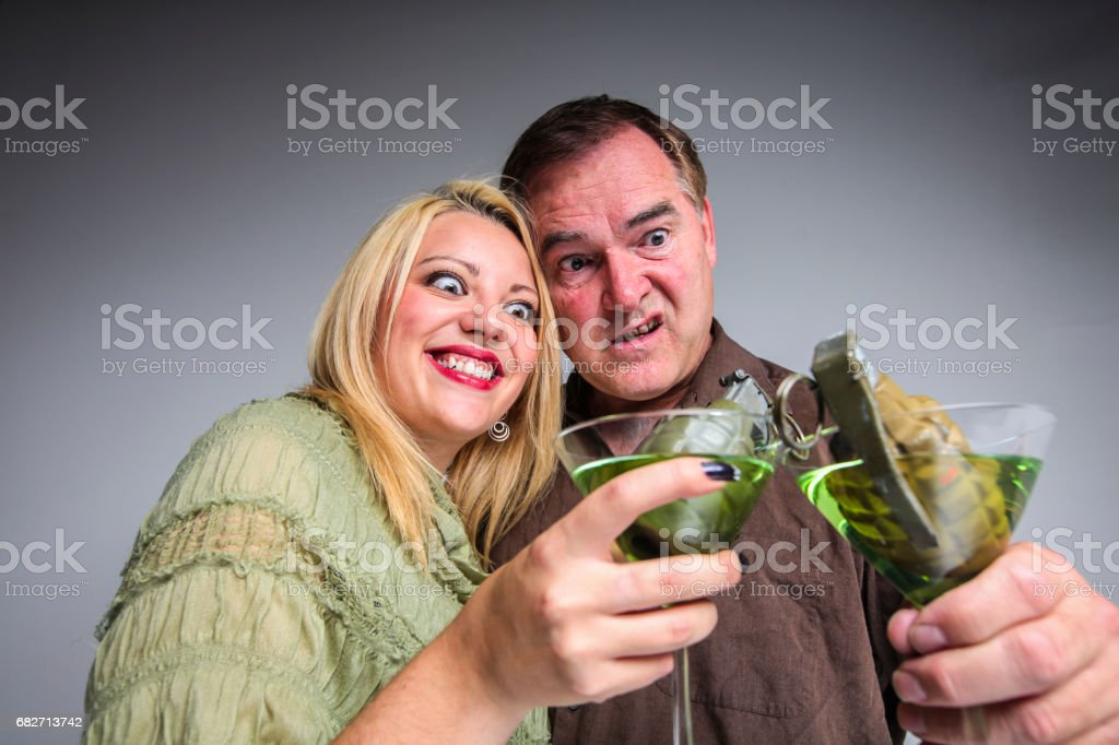 Humorous concept of an explosive relationship, may it be a couple or business, where a man and a woman are holding martinis, with each a grenade in their glass. stock photo