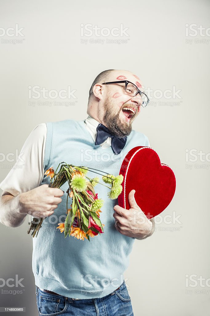 Humorous Man covered in Kisses and holding Bouquet of Flowers royalty-free stock photo