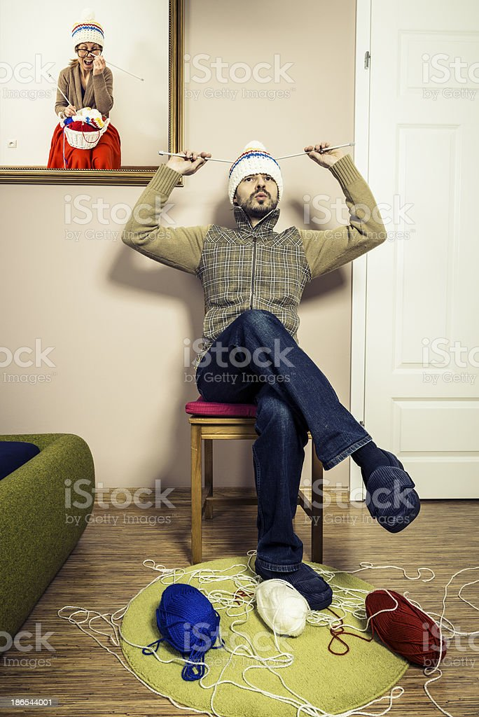 Humorous, man sitting on chair and knitting winter cap, interior royalty-free stock photo