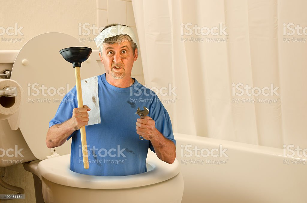 Humorous plumber inside toilet with tools and toilet paper stock photo