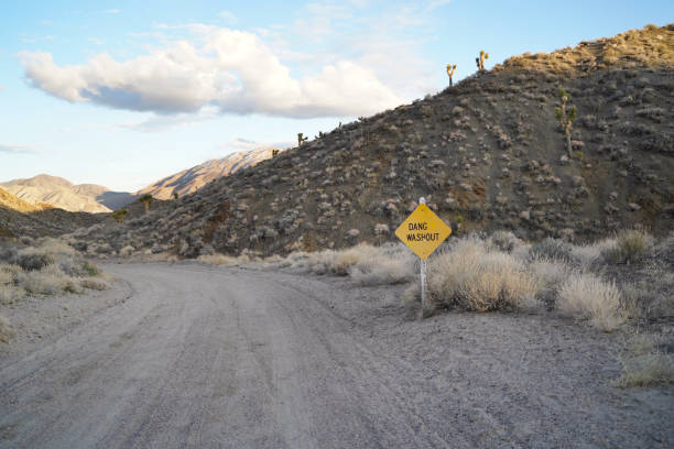 A humorous roadside sign warns of a rough driving conditions ahead. stock photo