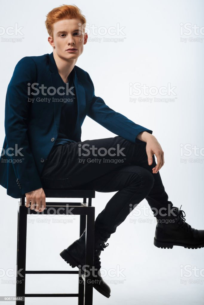 Humourless young man wearing a jacket stock photo