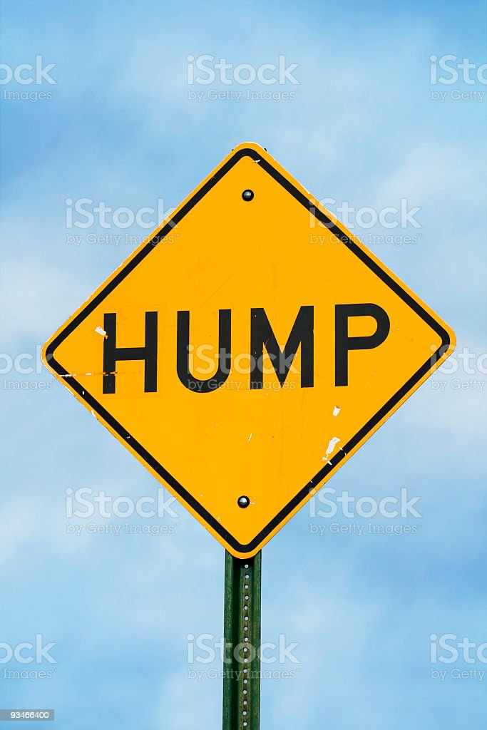 Hump on yellow road sign against blue sky stock photo
