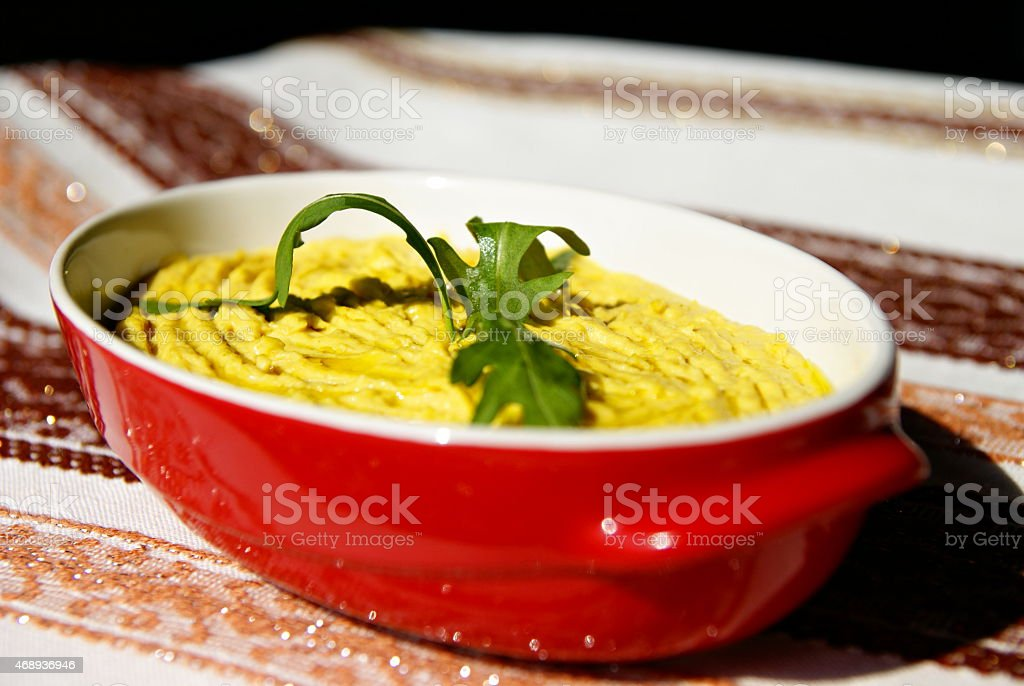 Humus paste with olive oil and chili, decorated with rucola stock photo