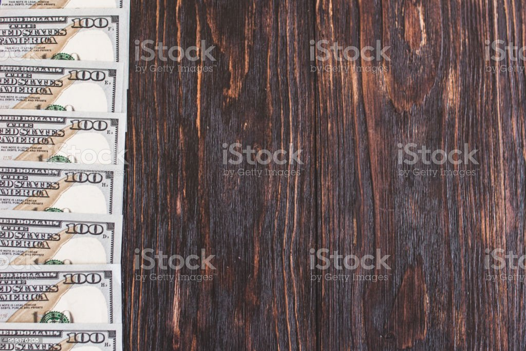 Hundred dollar bills on a wooden background. Blank space stock photo