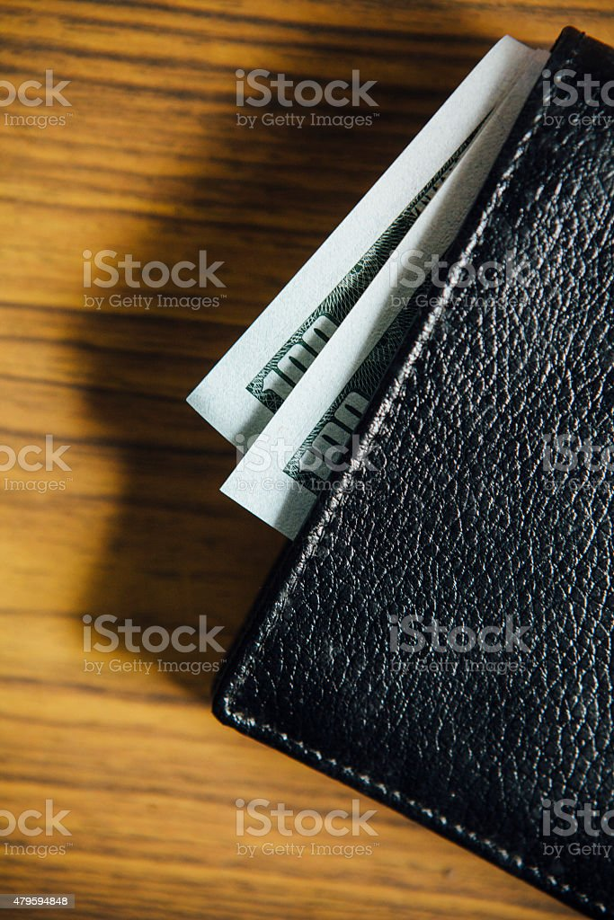 Hundred dollar bills sticking out from a wallet against a wooden...