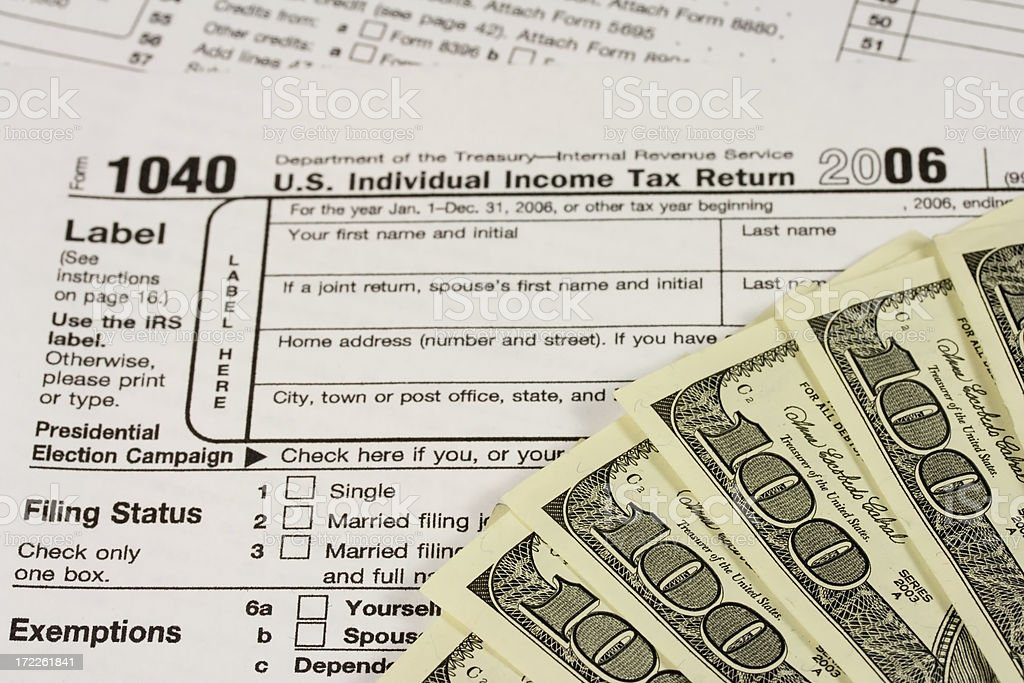 Hundred Dollar Bills with Income Tax Form 1040 stock photo