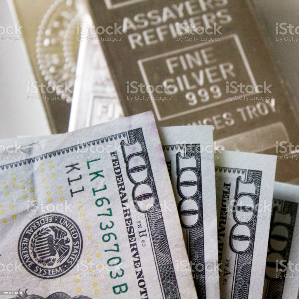 Hundred Dollar Bills with Silver Bars on Background stock photo