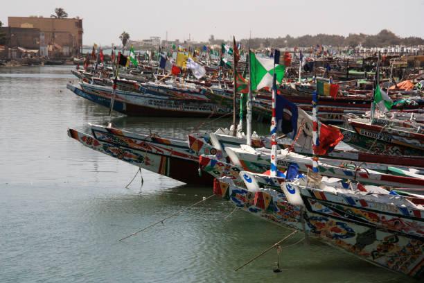 hundreds of colorful painted pirogues moored in the fisherman's wharf of saint-louis-du-sénégal - st louis стоковые фото и изображения