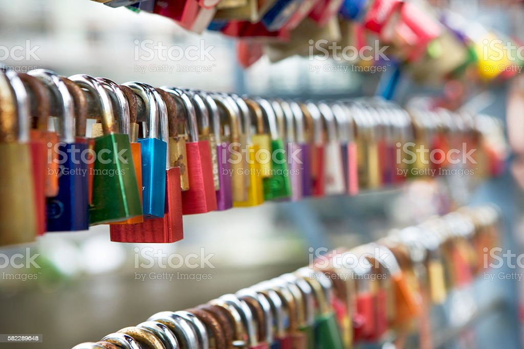 hundreds of multi colored locks hanging in a row stock photo
