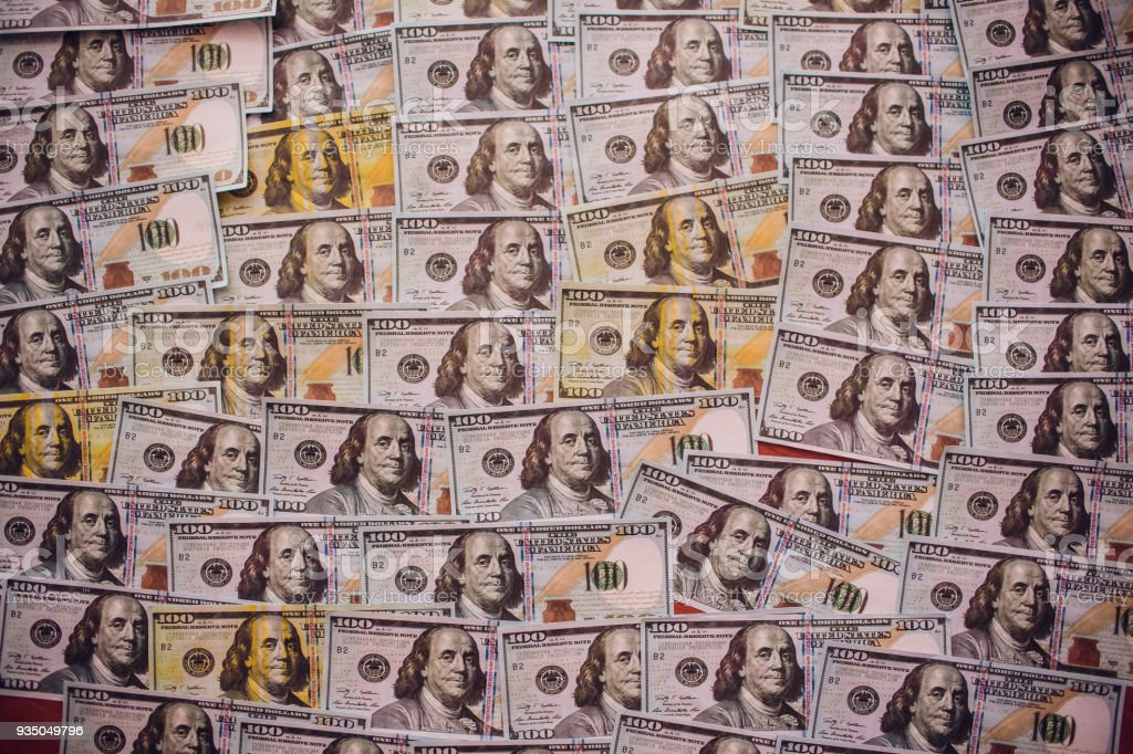 Hundreds of new Benjamin Franklin 100 dollar bills arranged randomly with the portrait facing uppermost in a closeup conceptual financial and monetary background stock photo