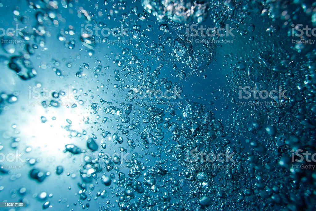 Hundreds of underwater air bubbles rising to water surface royalty-free stock photo