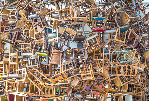 hundreds of vintage chairs stacked in a pile