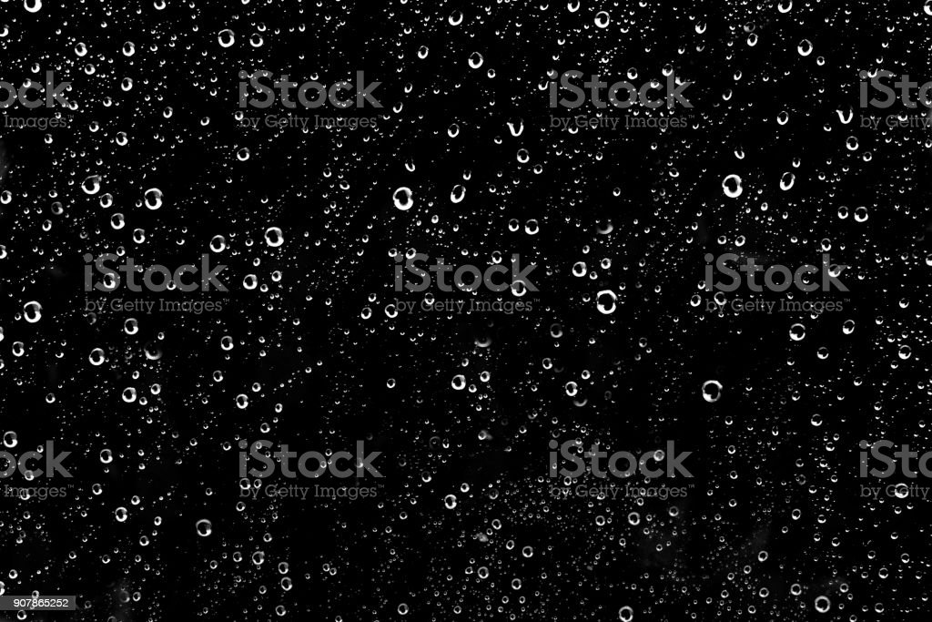 Hundreds of white rain drops on a glass window stock photo