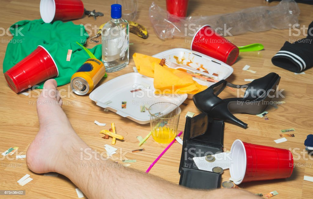 Hung over man passed out on the floor next day to a party, foot visible. Trash, food leftovers, clothes, high heels and bottles everywhere in messy house. stock photo