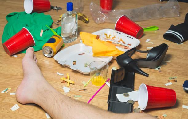 Planait sur l'homme évanoui sur le sol le jour suivant à une fête, des pieds visibles. Trash, restes de nourriture, des vêtements, des talons hauts et bouteilles partout dans la maison malpropre. - Photo